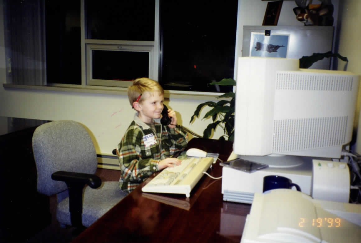 Boy Sitting at Computer and on the Phone